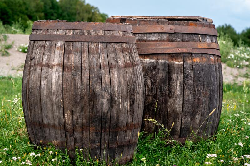 Two old barrels made of wood. Two old barrels or casks made of wood with rusty metal hoops standing on a green field royalty free stock photo