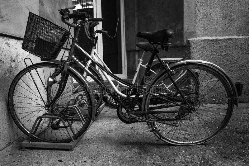 Two old bicycles park in the backyard of an old building stock image