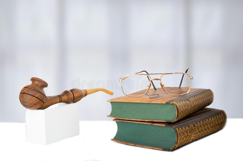 Two old books with a pair of glasses on them and a tobacco pipe. In front of bright background. The teachers day. Back to school. Space stock photo