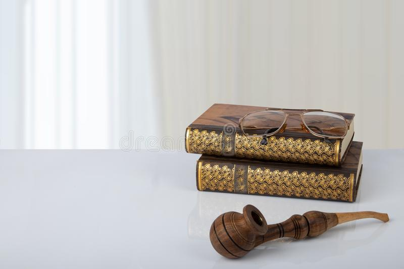 Two old books with a pair of glasses on them and a tobacco pipe. In front of bright background. The teachers day. Back to school. Space stock photography