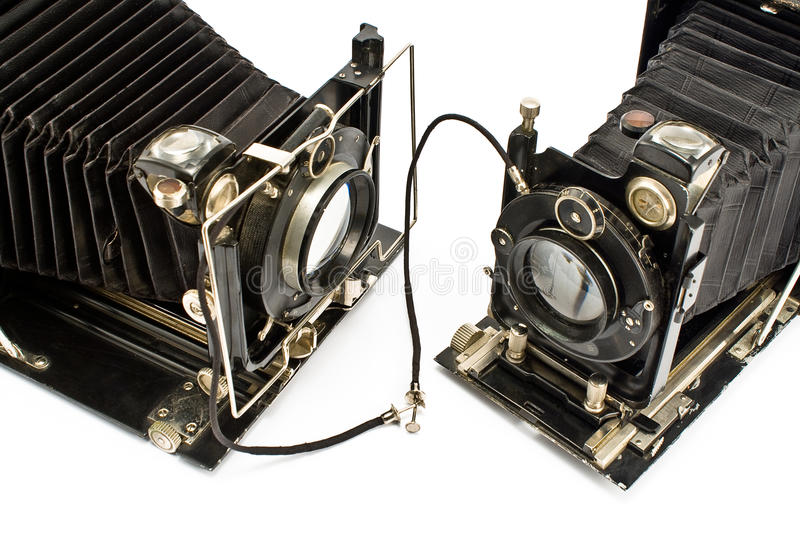 Two Old Cameras holding hands. Isolated on white stock images