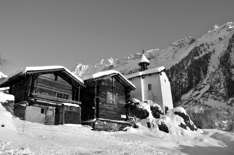 Two old chalets and a chapel in the snow. Two old wooden chalets and a chapel in the swiss mountains after a snow storm in monochrome stock image