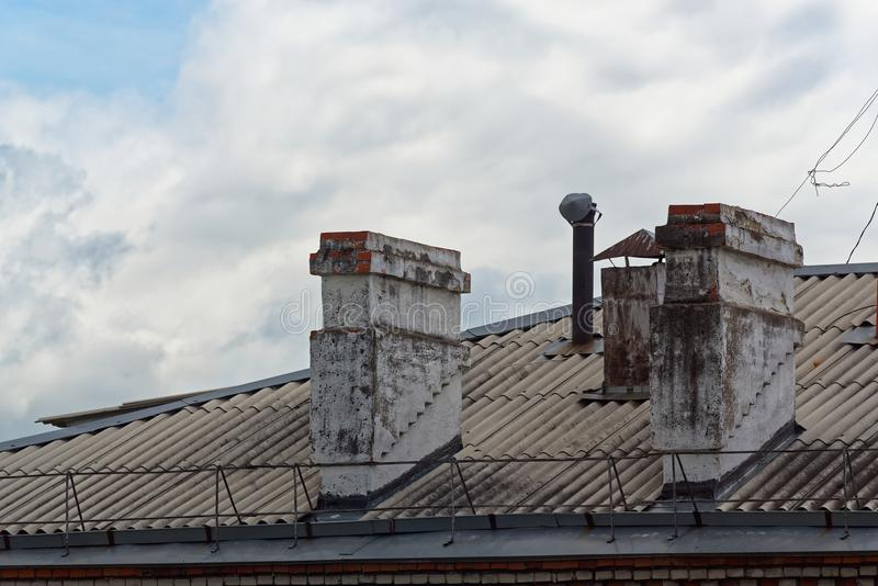 Two old chimneys on roof of an apartment house stock image