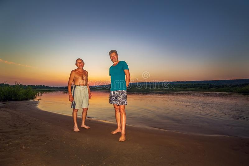 Two companions on a wild beach of the river against the backdrop of a sunset. Two old companions on a wild beach of the river against the backdrop of a sunset royalty free stock images