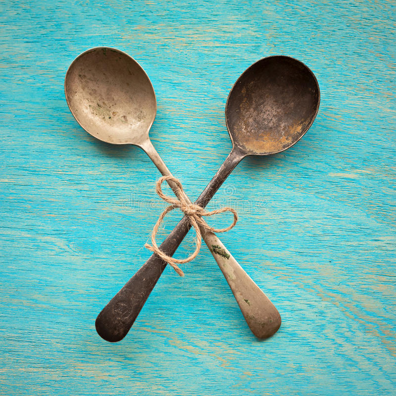 Two Old crossed vintage spoons on blue wooden background, top vi royalty free stock photos