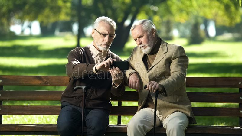 Two old friends making selfie, having fun in park, new modern technologies royalty free stock images