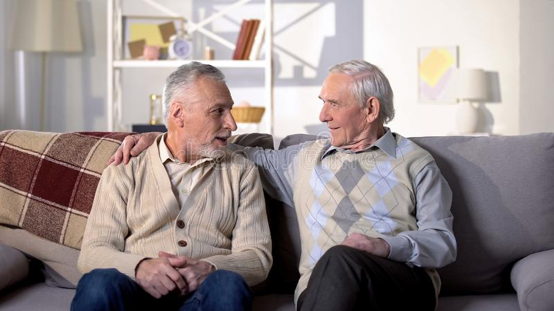 Two old friends talking having fun sitting on sofa, positive mood, conversation royalty free stock images