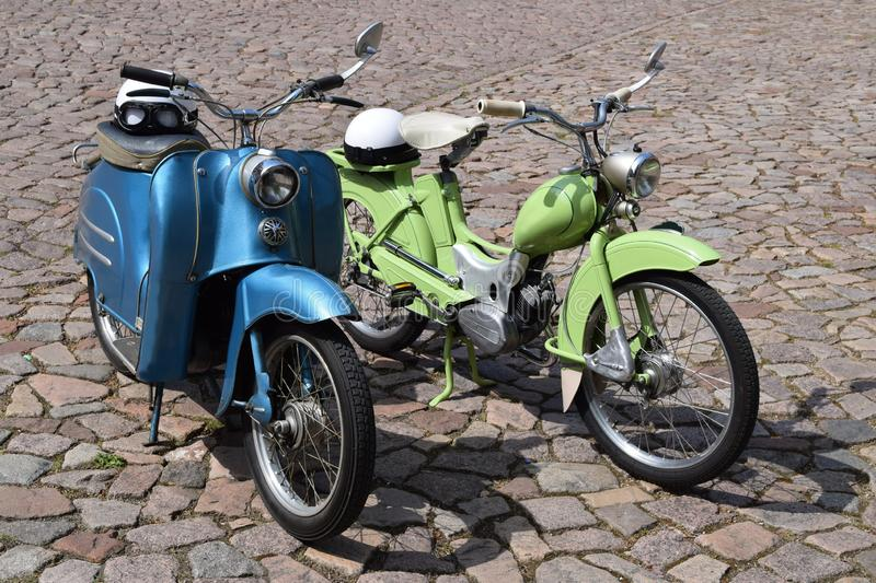 Two old, historic motorbikes in green and blue stock photos