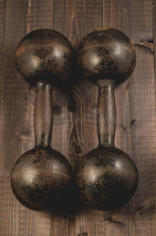 Two old iron dumbbell on a wooden dark background/two old iron d stock photos