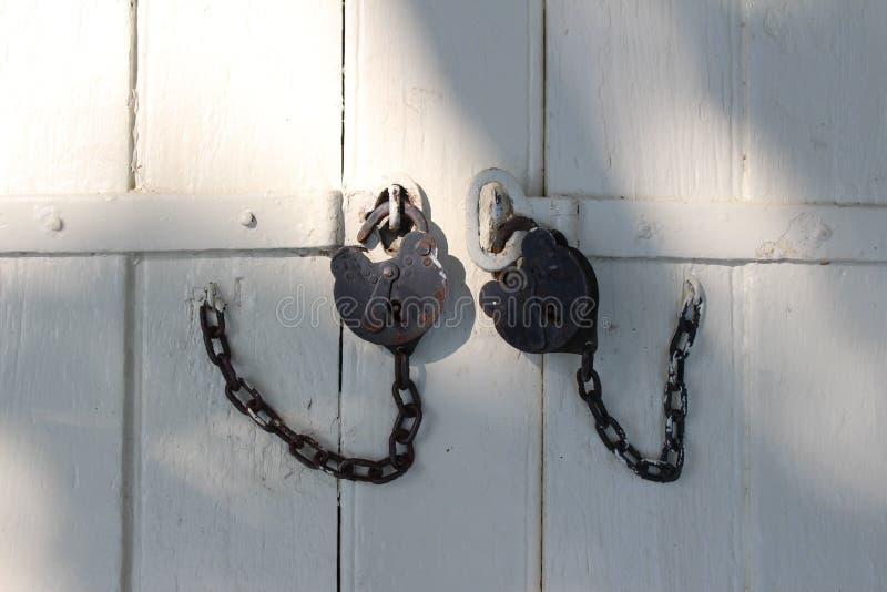 Black iron padlocks on the vintage wooden gate royalty free stock image