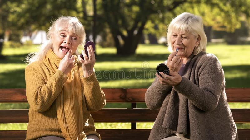 Two old ladies doing make up, sitting on bench in park, anti-age cosmetics stock image