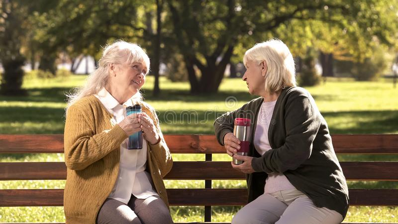 Two old ladies drinking hot tea from travel mugs, sitting on bench in sunny park royalty free stock photos
