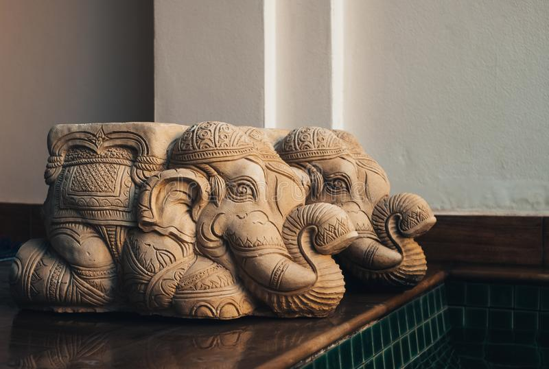 Two Old mortar elephant statue kneeling on the wooden floor inside swimming pool. At the home, Vintage stock photo