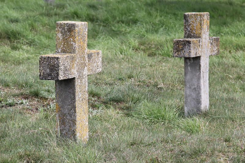 Two old nameless crosses in the military cemetery. Two old abandoned nameless crosses on graves overgrown with grass in a military cemetery royalty free stock images