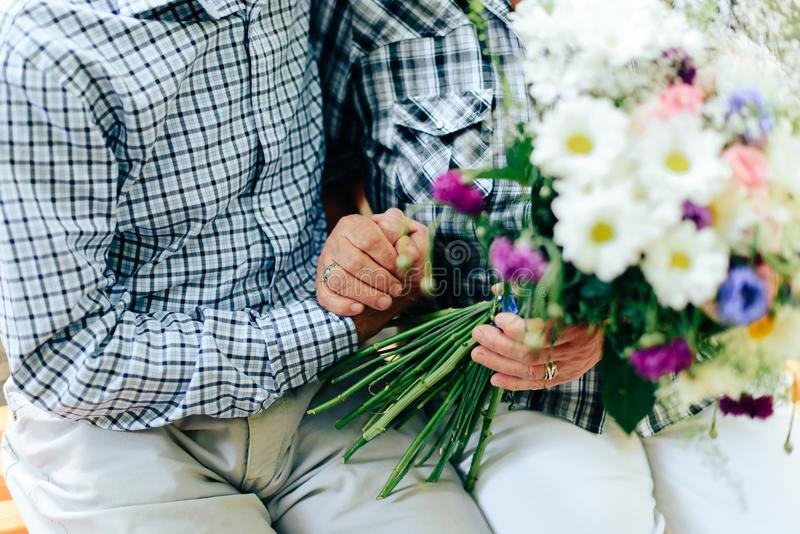 Two old people are sitting on a bench and holding each other`s hands against a beautiful bouquet of flowers. 1 stock image