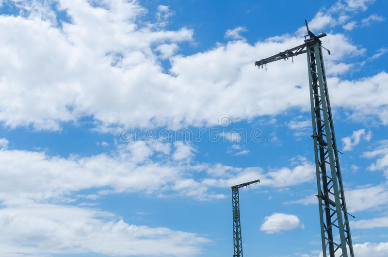 Two old railway masts in front of a dramatic cloudy sky. Two old railway masts building a metaphor for an unequal conversation or a potential to grow stock images