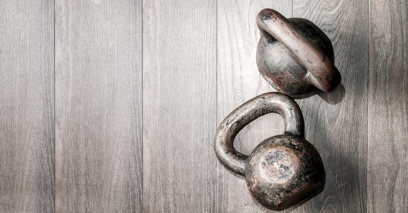Two old rusty and heavy kettle bells on the gym floor ready ford hard core fitness workout training view from above with copy spac. E, kettlebell fitness sport stock photo