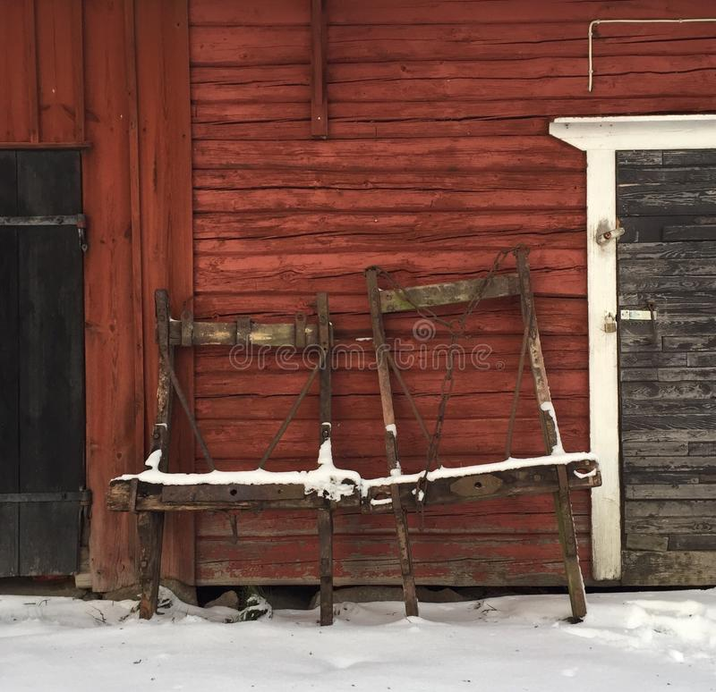 Two old horse drawn sleighs. For logging leaning against a red painted log wall royalty free stock image