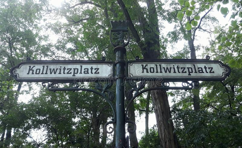 Two old street signs to the Kollwitzplatz. Background, beautiful, berlin, blue, city, destination, direction, forest, germany, green, hiking, landscape royalty free stock photos