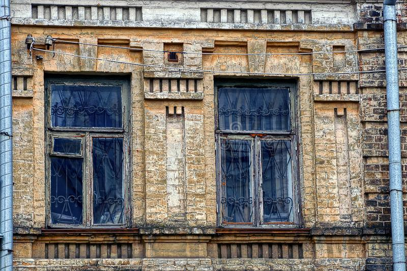 Two old windows on the brick wall of the building. The old windows on the wall of the apartment house royalty free stock photo
