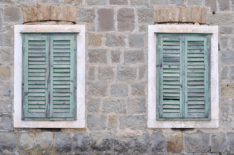 Two old windows with closed shutters on an old house. Two old windows with blue closed shutters on an old house. Vintage background, texture stock images