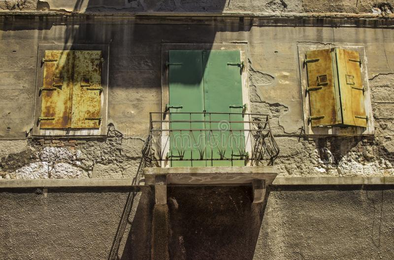 Two old windows and a green balcony door on the old building. Two old windows and a balcony. A green old door from a balcony on an old stone building royalty free stock photos