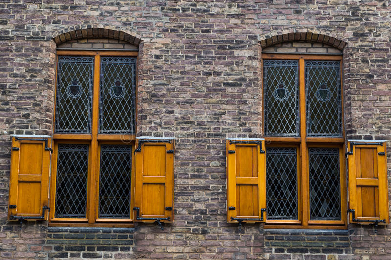 Two old windows with iron bars and wooden shutters. Two old windows with iron lattice and wooden shutters on brick facade of the house royalty free stock photos