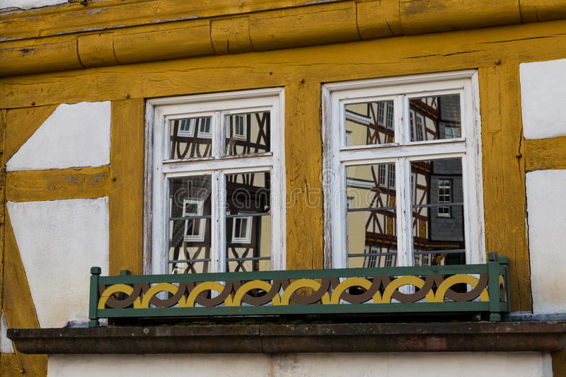 Two old windows. Two windows on old multicolored wooden country house. Windows reflect old houses royalty free stock photo