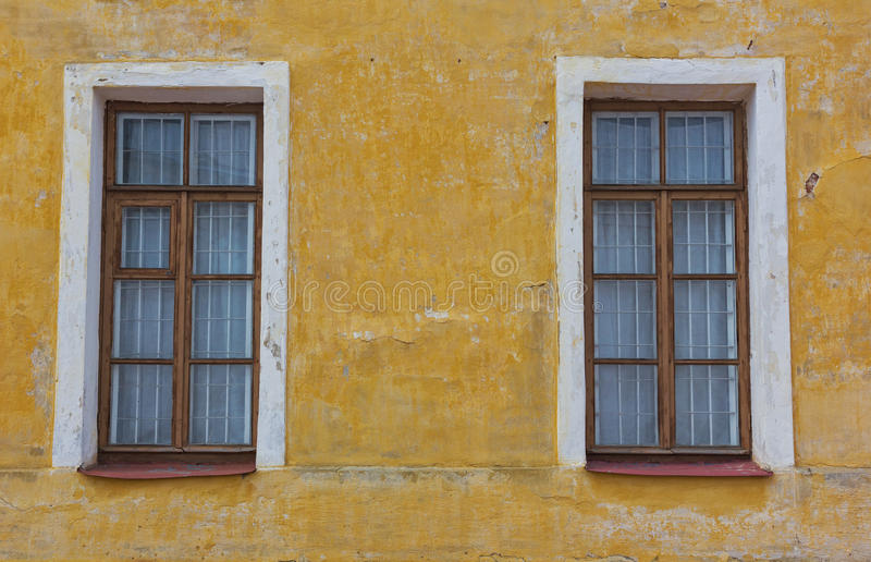 Two old windows on the yellow wall royalty free stock photo