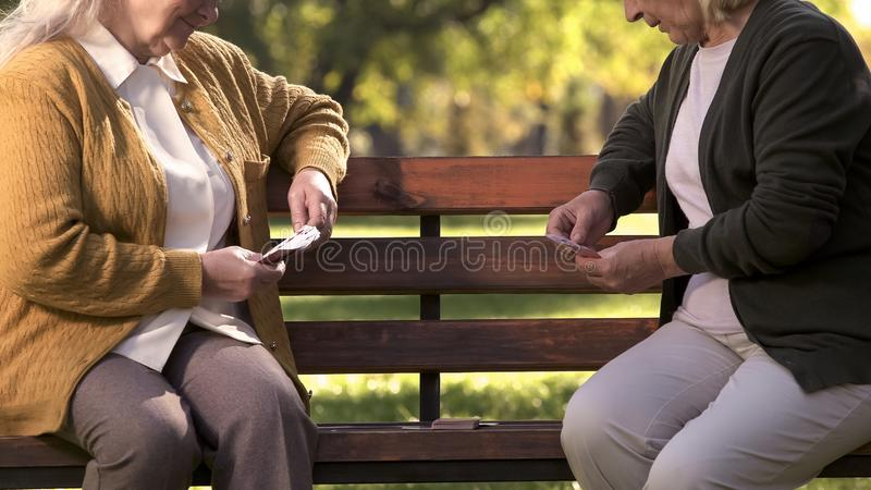 Two old women enjoying cards playing on bench in park, elderly friends leisure royalty free stock photography