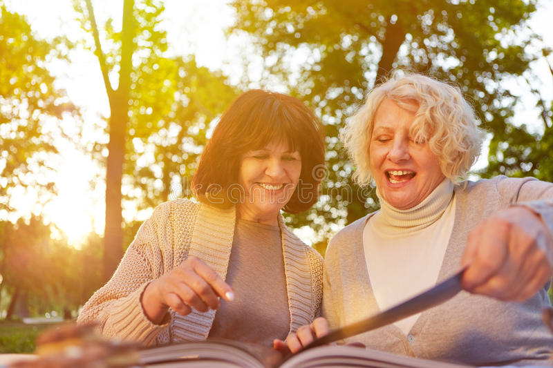 Two old women reading recipes in a book royalty free stock photography