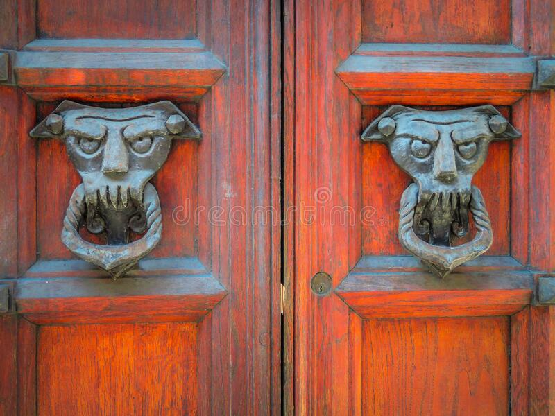 Two old and worn italian doorknockers shaped like demons on red wooden door stock photo