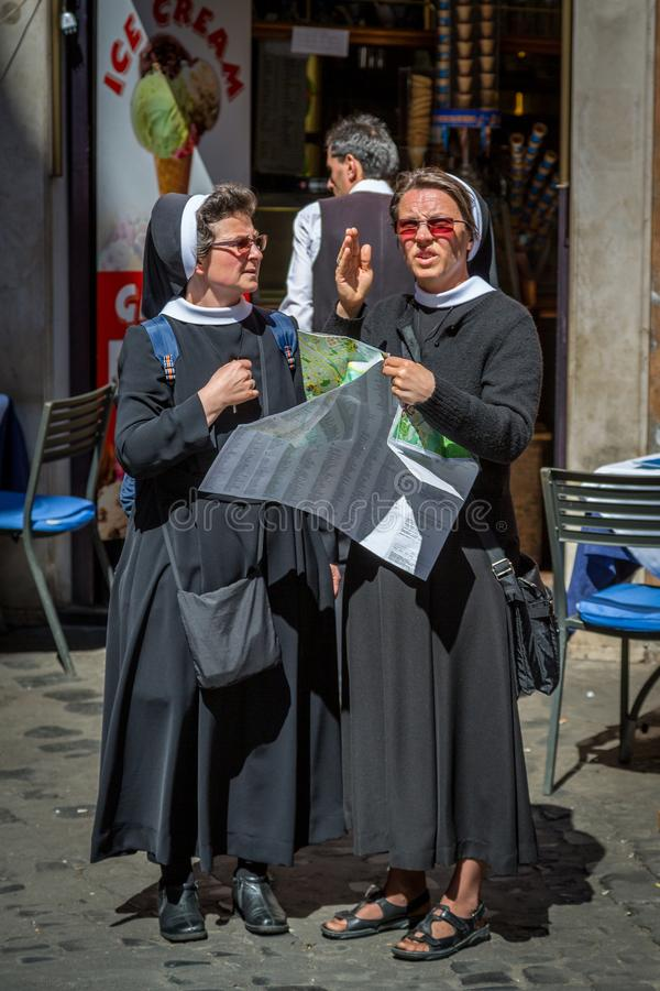 Two older nuns holding a city map and talking to each other. royalty free stock images