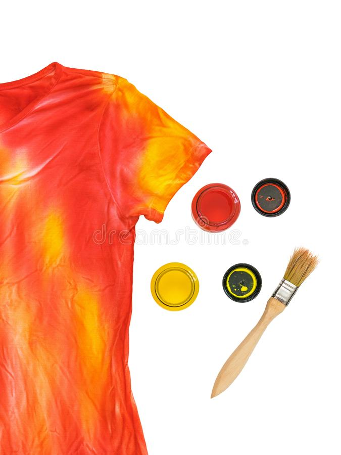 Two open cans of paint, a brush and a t-shirt in the style of tie dye on a white background. royalty free stock photos