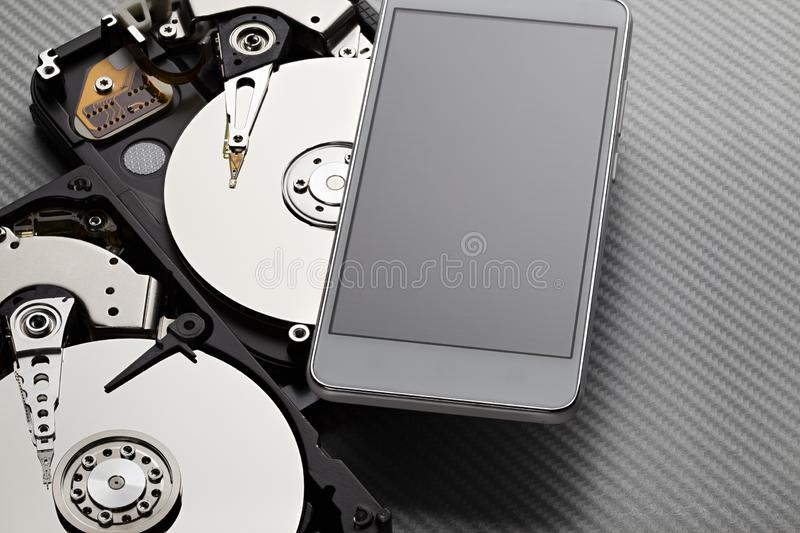 Two opened hard disk drive and modern smartphone on carbon fiber background stock photos