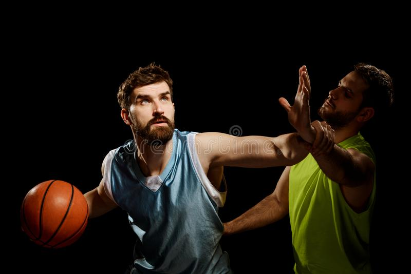 Two opposing basketball players. On black. Man driving through another player`s block and looking at the basket stock images