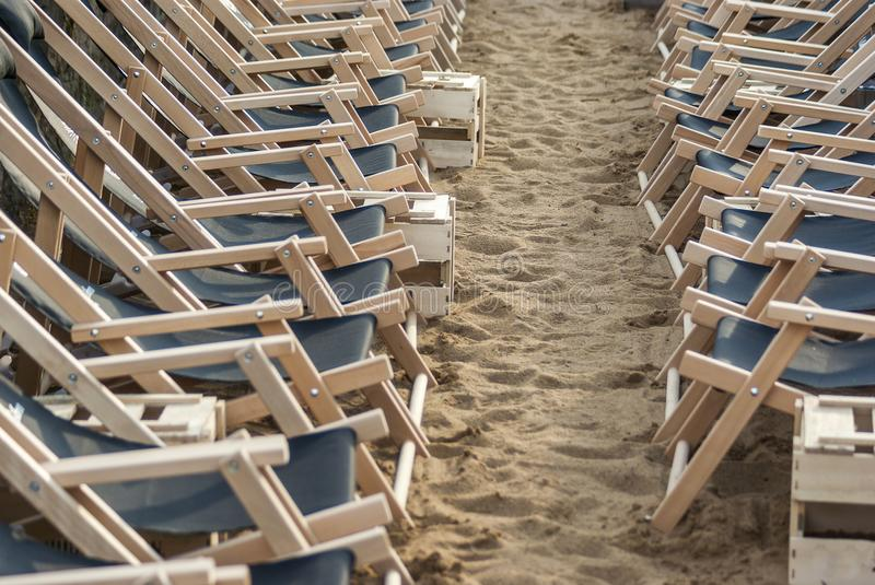 Two opposing rows of suspended empty deck chairs in rows lined up in order on the beach in the sand.  royalty free stock photos