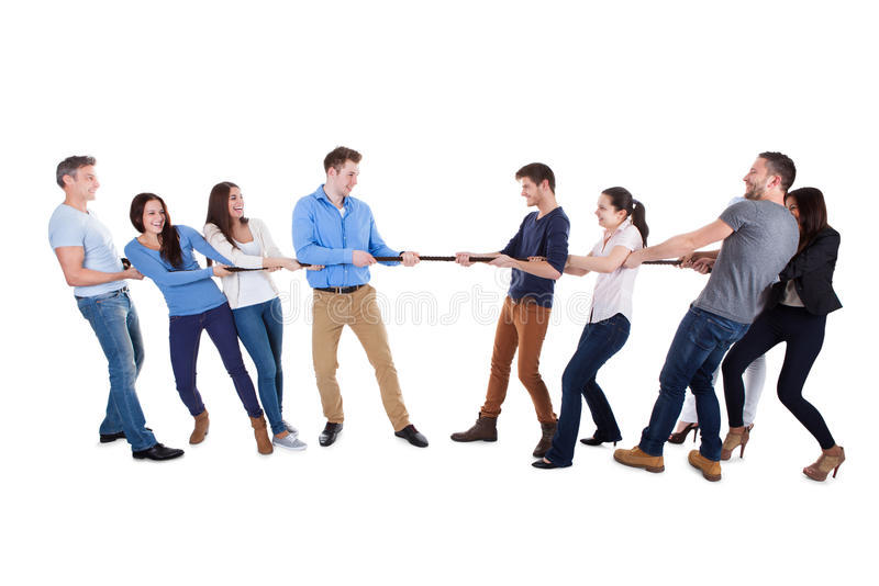 Two opposing teams having a tug of war. Pulling on opposite ends of a rope in a display of strength conceptual of competition challenge and determination on royalty free stock photos