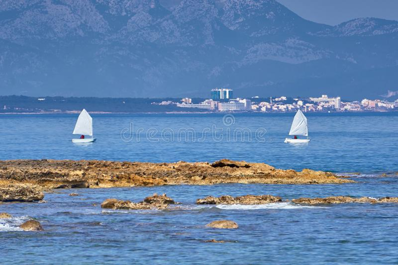Two Optimist Dinghies Crossing Alcudia Bay. With Can Picafort Hotels in The Background Majorca Spain stock image