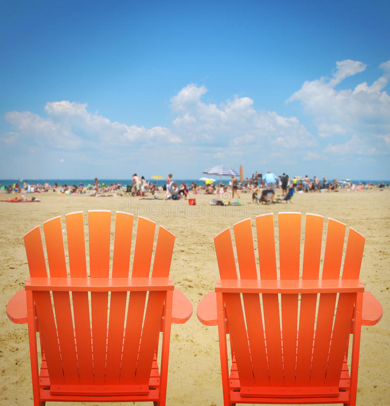 Two Orange Beach Chairs in Sand stock photography