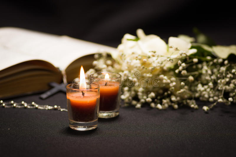 Two orange candles with a blurred rosary beads over a holy bible and small flowers, black background stock image