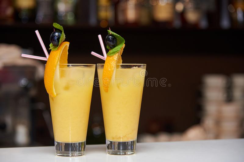 Two orange cocktails decorated with a slice of orange, olive and mint royalty free stock photography