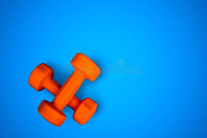 Two orange dumbbells, fitness equipment on blue background stock photography
