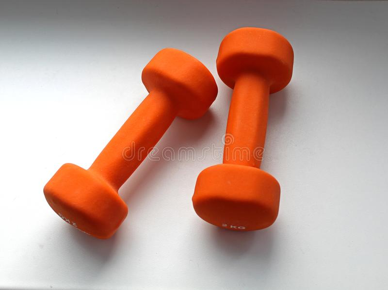 Two orange dumbbells of 2 kg each one on a gray background stock image