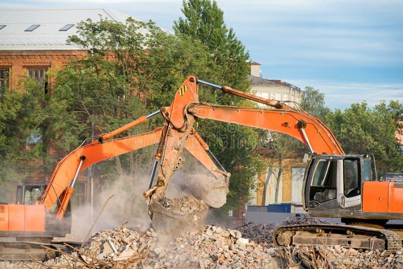Two orange excavators working on the debris of a demolished building stock image