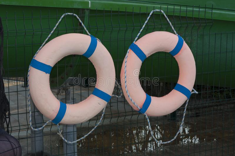 Two orange lifebuoys on hanging on a wooden wall of a boat station photo stock photo