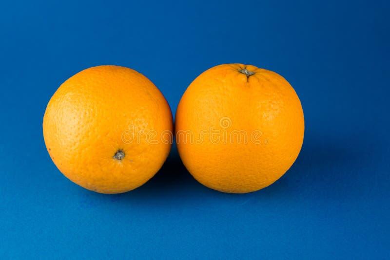 two orange oranges lying on a blue background royalty free stock photo