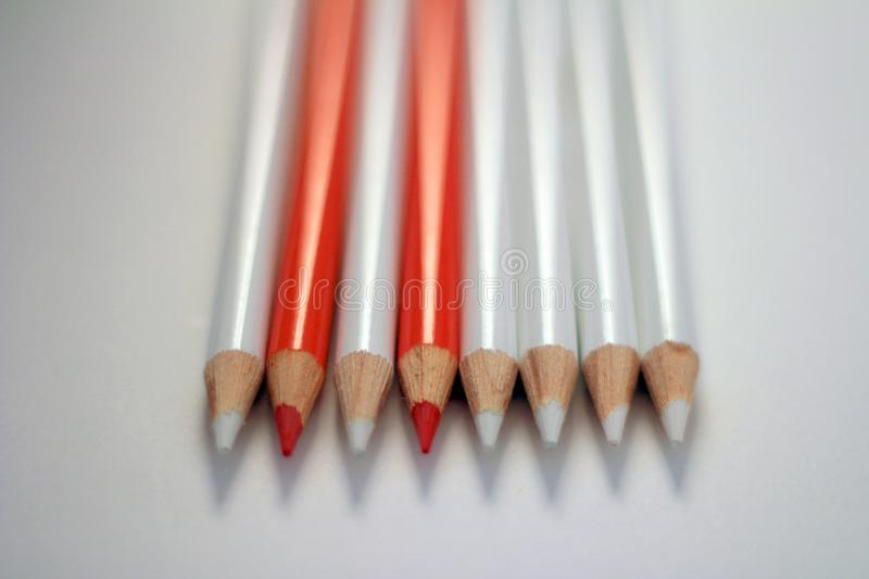 Two orange pencils between white pencils stock photo