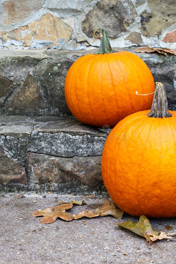 Two orange pumpkins decorating the entryway stairs to a home. royalty free stock photo