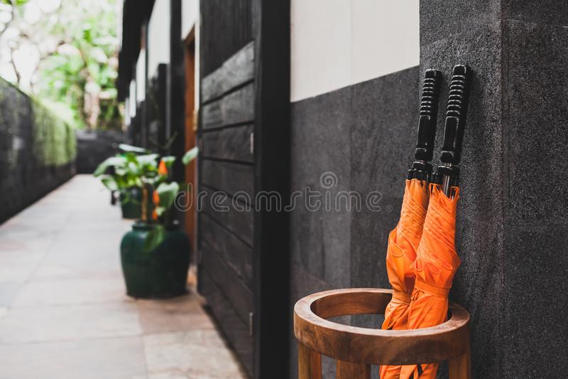 Two orange umbrellas in wooden basket outside room. Hotel. Resort service royalty free stock images